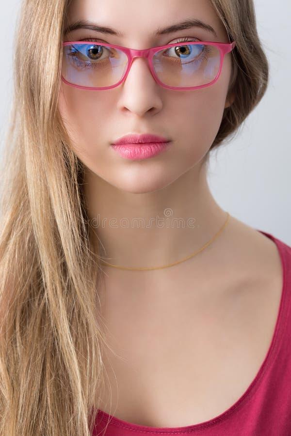 Porträt des jungen wooman mit rosa Gläsern, den Lippen und Hemd lizenzfreie stockfotografie