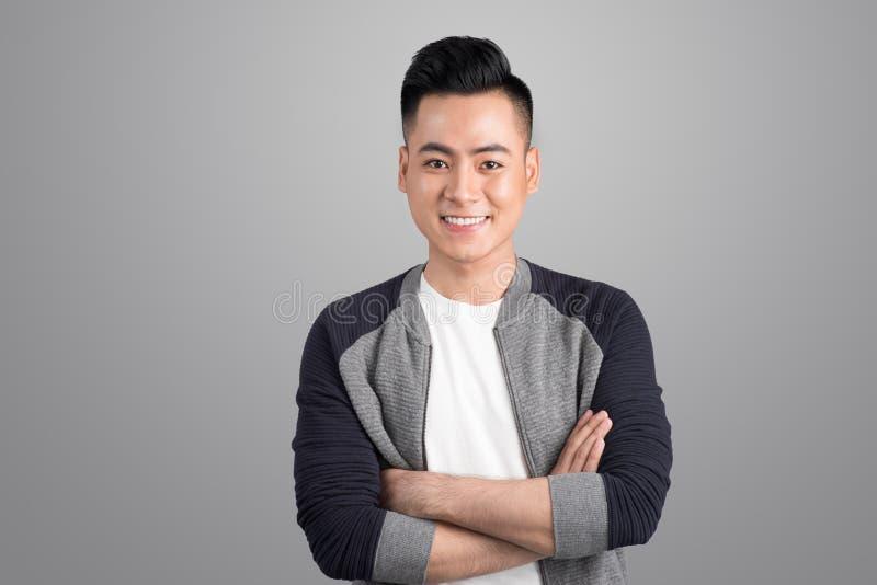 Porträt des kühlen hübschen asiatischen Mannes mit den Armen gekreuzt stockfotografie