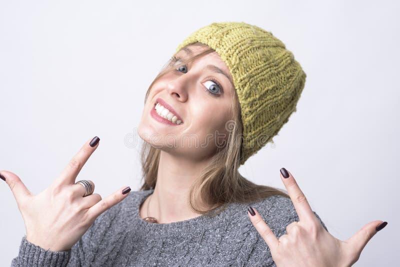 Porträt des kühlen jungen flippigen Mädchens mit der gelben Kappe, die Schwermetallhornzeichen zeigt lizenzfreie stockbilder
