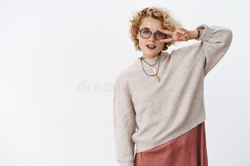 Porträt des kühlen und stilvollen jungen Hippie-Mädchens in der modischen Strickjacke und in den Gläsern, die Friedensgeste oder  stockbild