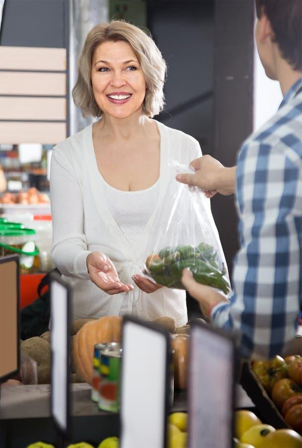 Porträt des kaufenden grünen Paprikas der gewöhnlichen reifen Frau im Lebensmittelgeschäft stockfotos