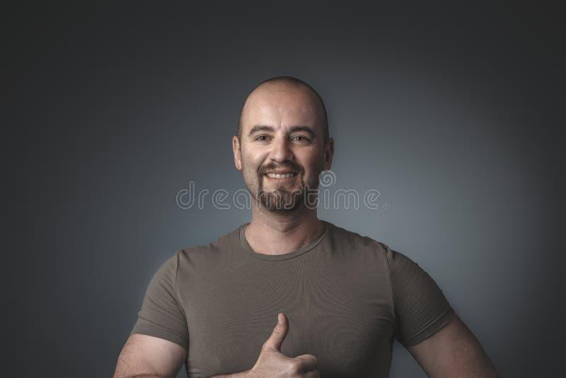 Porträt des kaukasischen positiven Manndaumens oben stockbilder