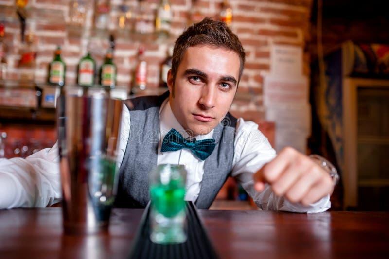 Porträt des Kellners hinter Bar mit Cocktail bearbeitet und trinkt stockfoto