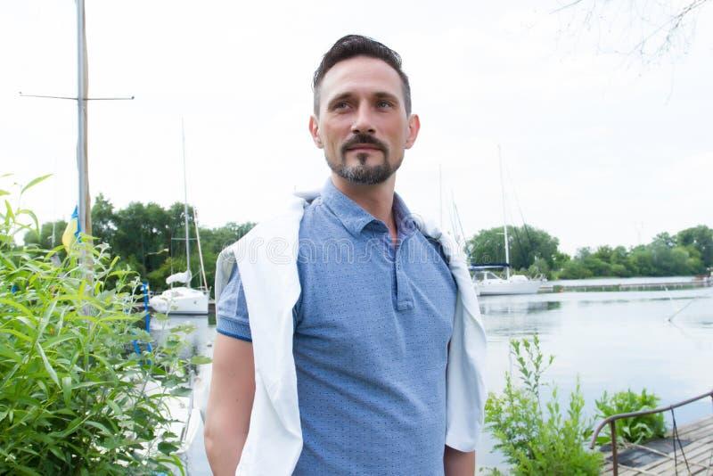 Porträt des Kerls nahe von Fluss mit Booten Gut aussehender Mann bevor dem Segeln auf Fluss Bemannen Sie ` s Art und Polo und Spi lizenzfreie stockfotos
