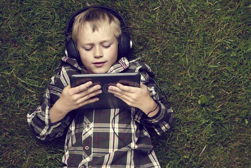 Porträt des Kinderblonden Jungen, der mit einem digitalen Tablet-Computer draußen liegt auf Gras spielt stockbild