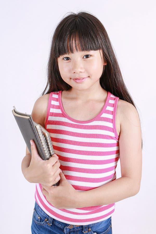 Porträt des kleinen asiatischen Mädchens, welches das Buch an lokalisiert auf weißem Hintergrund hält stockfoto
