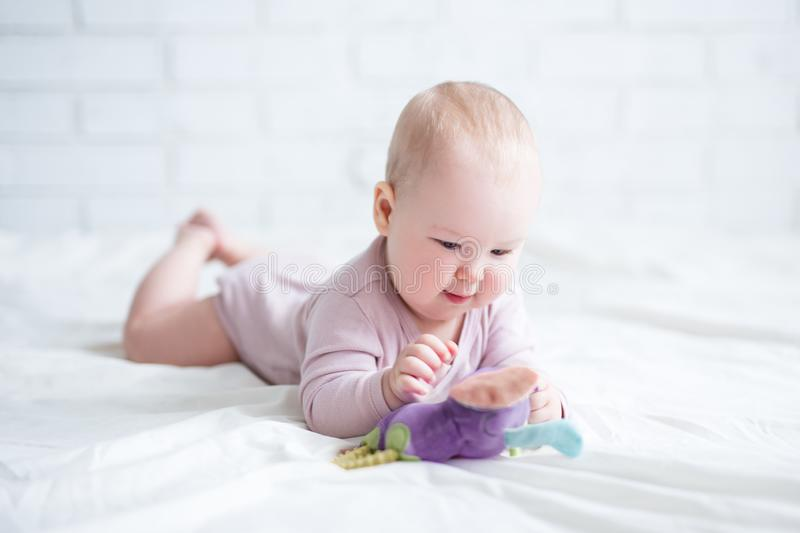 Porträt des kleinen Babys liegend auf dem Bett mit Spielzeug lizenzfreie stockfotografie
