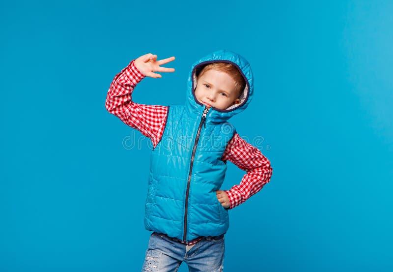 Porträt des kleinen Jungen in einem Hemd und in einer Weste, die Frieden durch Finger zeigen lizenzfreie stockbilder