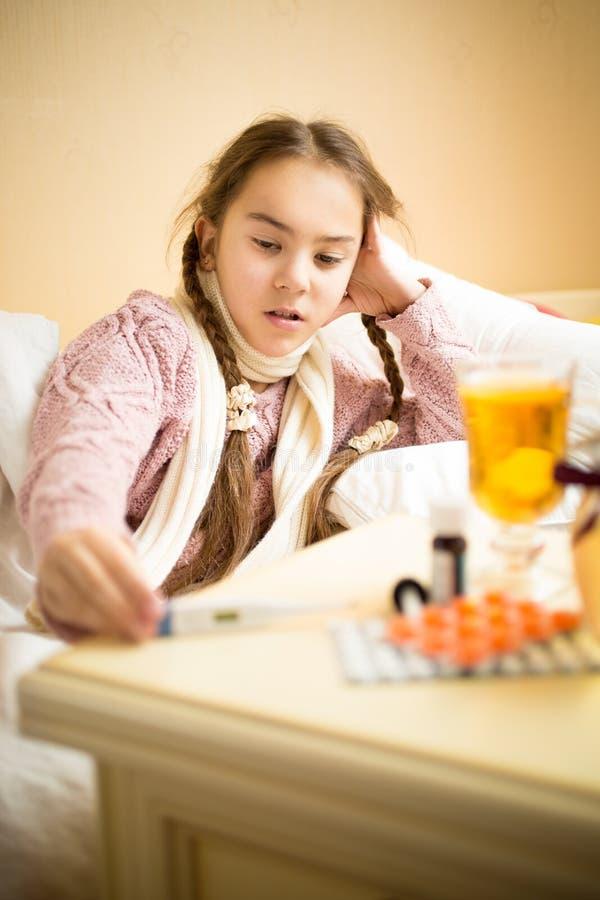 Porträt des kleinen kranken Mädchens, das im Bett liegt und thermom betrachtet lizenzfreie stockfotos