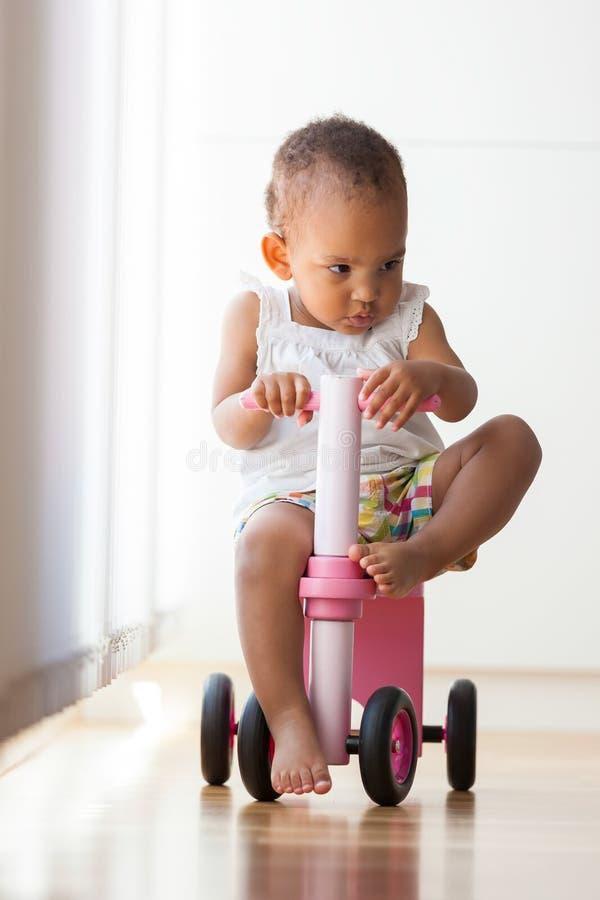 Porträt des kleinen Mädchens des kleinen Afroamerikaners, das ein Fahrrad reitet - lizenzfreie stockbilder