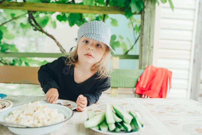 Porträt des kleinen Mädchens in einer Kappe hinter einem Speisetische an der Datscha lizenzfreie stockfotografie
