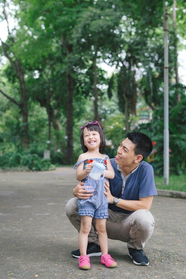 Porträt des kleinen Mädchens ihren Vati mit Natur, Familie Co umarmend stockfotos