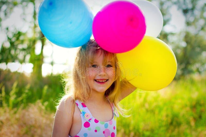 Porträt des kleinen Mädchens mit Ballonen im Park lizenzfreie stockbilder