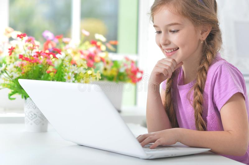 Porträt des kleinen Mädchens mit modernem Laptop stockbilder