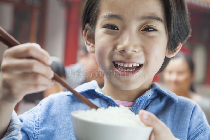 Porträt des kleinen Mädchens Reis essend lizenzfreie stockfotografie