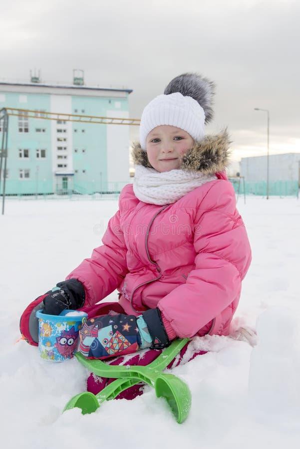 Porträt des kleinen Mädchens sitzend auf schneebedecktem Boden lizenzfreie stockfotos