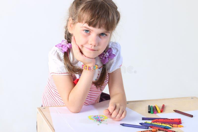 Porträt des kleinen Mädchens sitzt bei Tisch mit Papierblättern lizenzfreie stockbilder