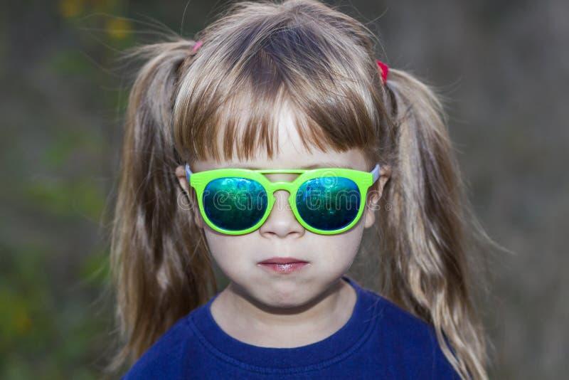 Porträt des kleinen modernen Mädchens in der grünen Sonnenbrille draußen lizenzfreies stockfoto