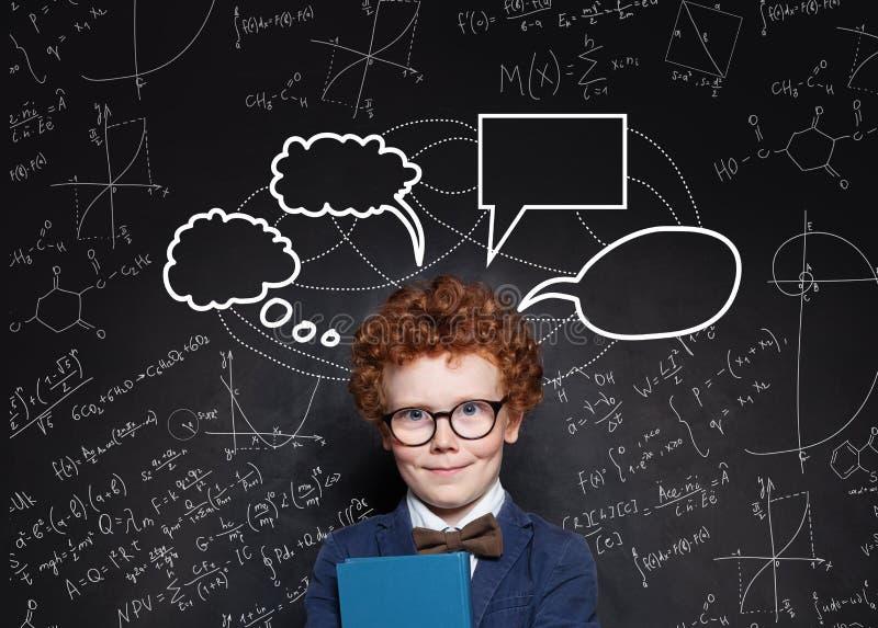 Porträt des klugen kleinen Jungen und der leeren denkenden Wolkenblasen auf Tafelhintergrund lizenzfreie stockfotos