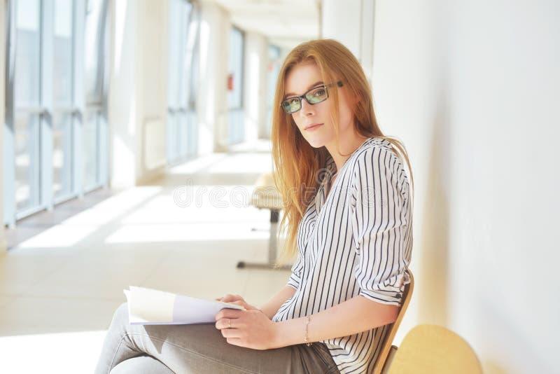 Porträt des klugen Studenten mit offenem Buch es im College lesend Schöne Studentin in einer Universität, Frau in den Brillen stockbild