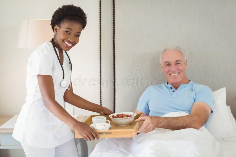 Porträt des Krankenschwesterumhüllungsfrühstücks zum älteren Patienten stockfotos