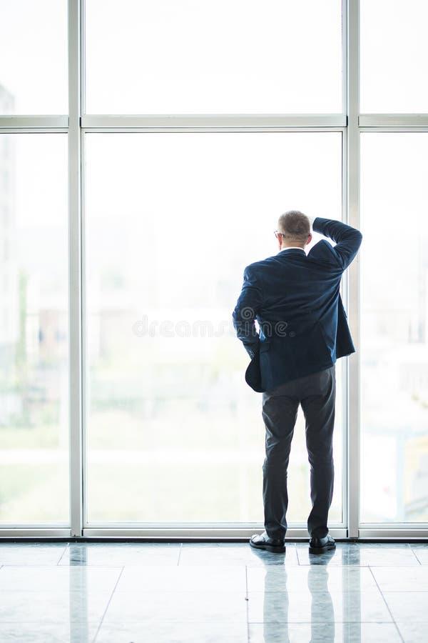 Porträt des lächelnden älteren Geschäftsmannes, der aus Bürofenster mit seiner Hand hinter seinem heraus zurück schauend steht lizenzfreie stockfotografie