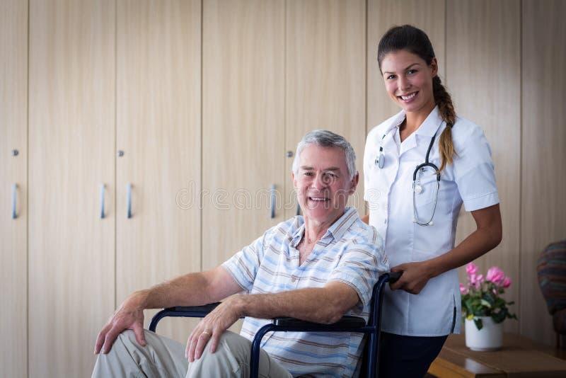 Porträt des lächelnden älteren Mannes und der Ärztin im Wohnzimmer lizenzfreie stockfotos