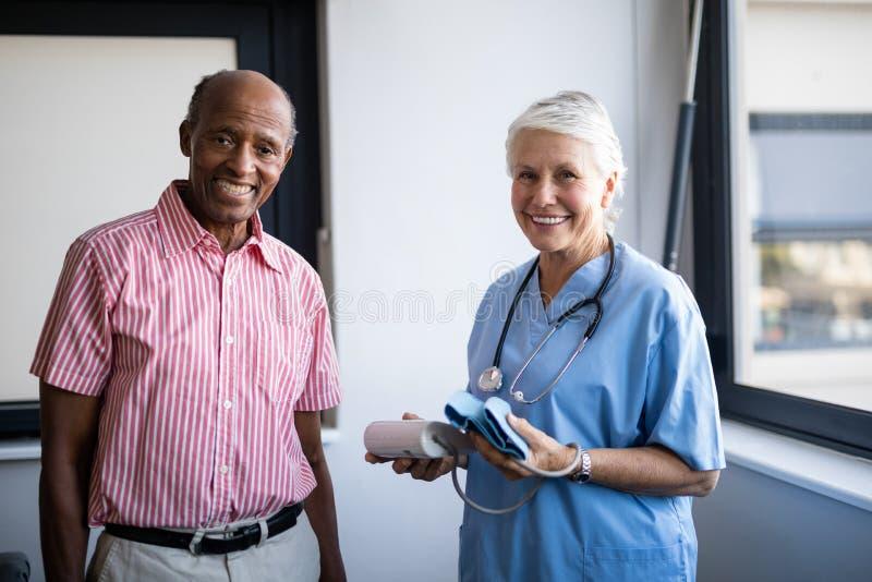 Porträt des lächelnden älteren Mannes und der Gesundheitswesenarbeitskraft stockfotografie