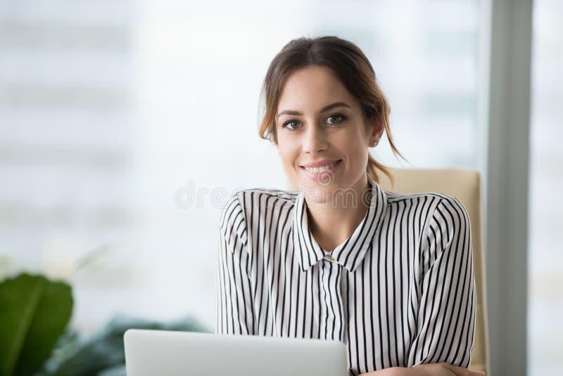 Porträt des lächelnden überzeugten weiblichen Chefs, der Kamera betrachtet stockfoto