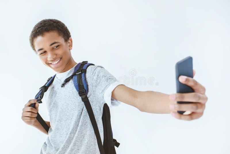 Porträt des lächelnden Afroamerikanerteenagers, der selfie auf Smartphone nimmt stockbilder