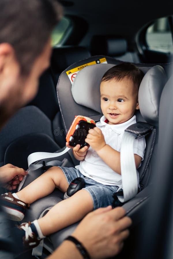 Porträt des lächelnden Babys und des Vaters im Autokindersitz lizenzfreies stockbild