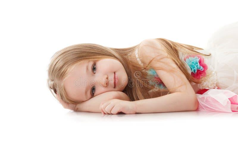 Porträt des lächelnden entzückenden Mädchens, das im Studio liegt stockbilder