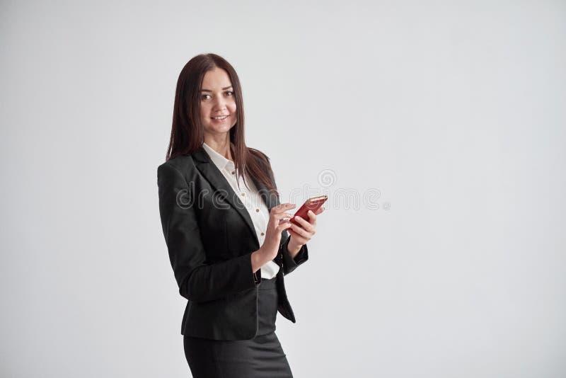 Porträt des lächelnden Geschäftsfrautelefons, das im Büro spricht lizenzfreie stockbilder