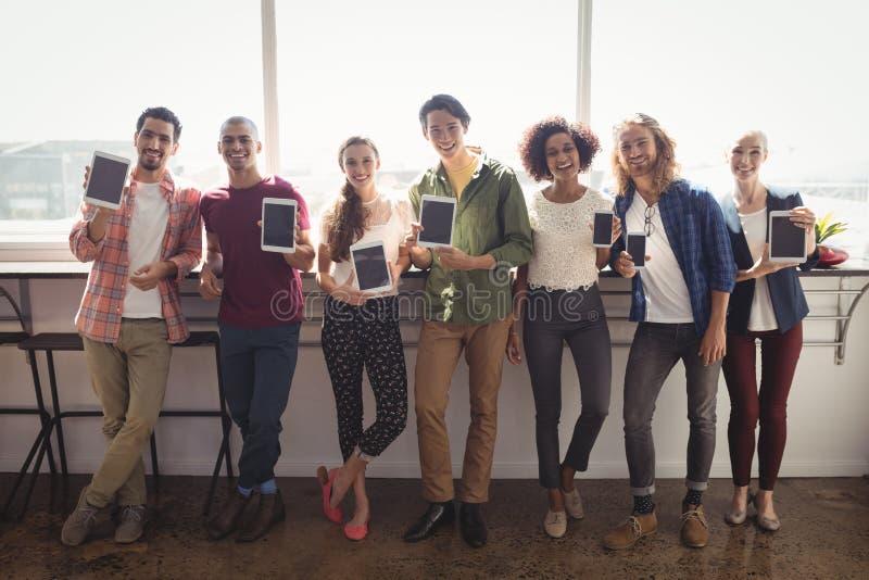 Porträt des lächelnden Geschäftsteams, das Technologien im kreativen Büro zeigt lizenzfreies stockfoto