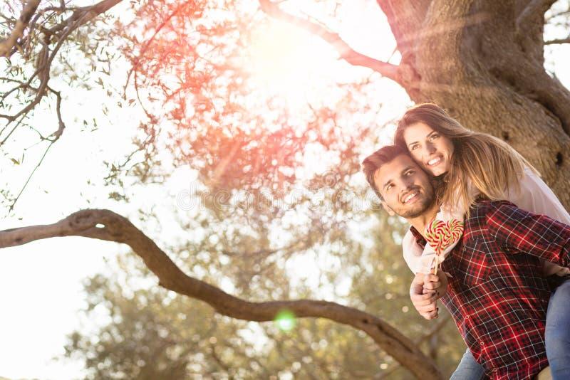 Porträt des lächelnden gutaussehenden Mannes piggyback gebend seiner Freundin in der Natur lizenzfreies stockbild