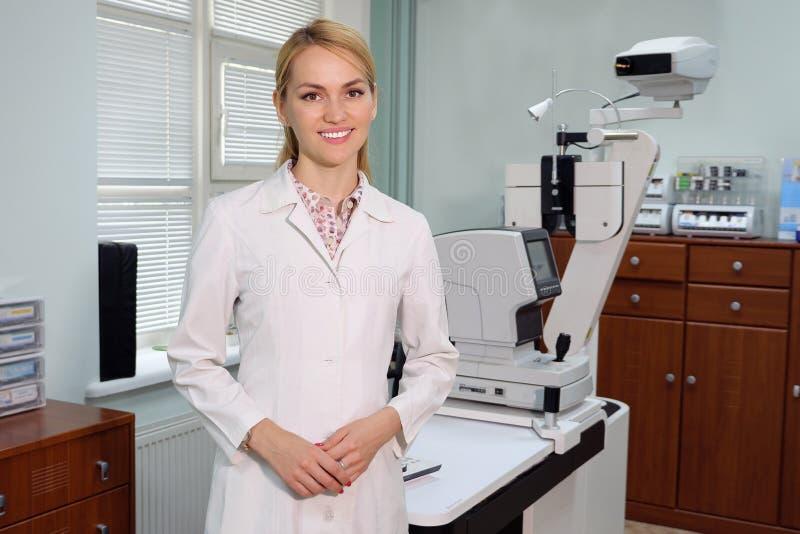 Porträt des lächelnden hübschen Augenarztes, der mit ophthalmologic Gerät im Kabinett steht stockfotografie