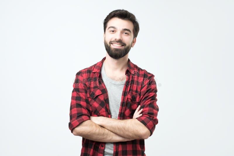 Porträt des lächelnden hübschen hispanischen Mannes in der karierten Hemdstellung mit den gekreuzten Armen stockfotografie
