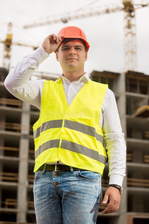 Porträt des lächelnden Ingenieurs im Hardhat, der gegen das Arbeits c aufwirft stockfotos