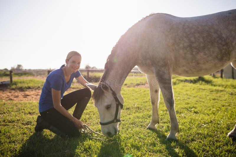 Porträt des lächelnden Jockeys Pferd an der Scheune streichend stockfotografie