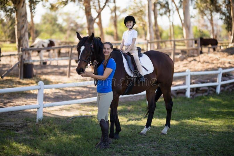 Porträt des lächelnden Jockeys und des Mädchens mit Pferd lizenzfreie stockfotografie