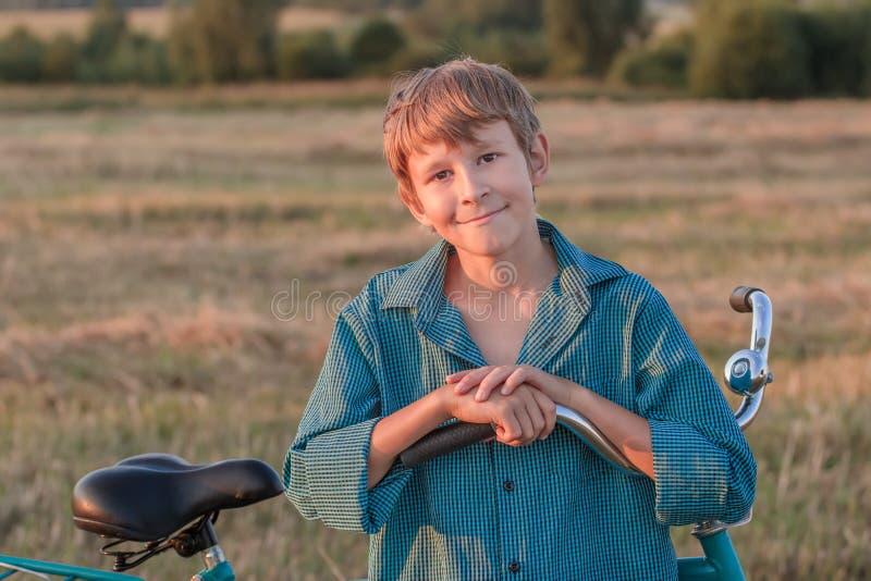 Porträt des lächelnden Jugendlichjungen mit Fahrrad stockbilder