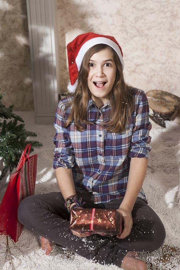 Porträt des lächelnden Jugendlichmädchens in Sankt-Hut, der Weihnachten hält stockfotografie