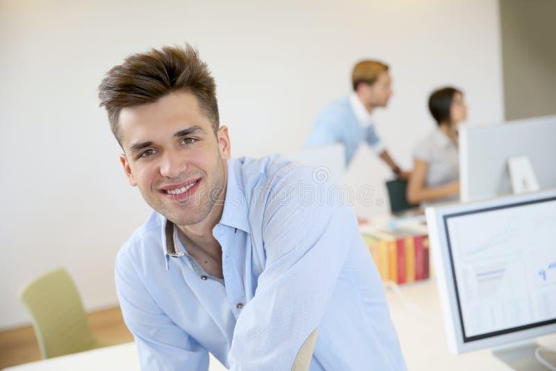 Porträt des lächelnden jungen Büroangestellten stockfotos