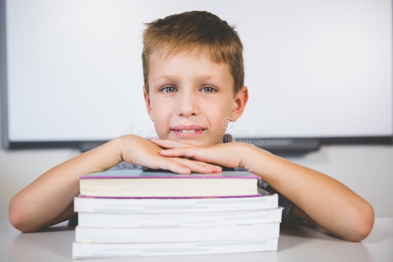 Porträt des lächelnden Jungen lehnend auf Stapel Büchern im Klassenzimmer stockfotografie