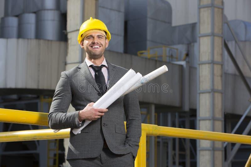 Porträt des lächelnden jungen männlichen Architekten, der Pläne außerhalb des Gebäudes hält stockfotografie