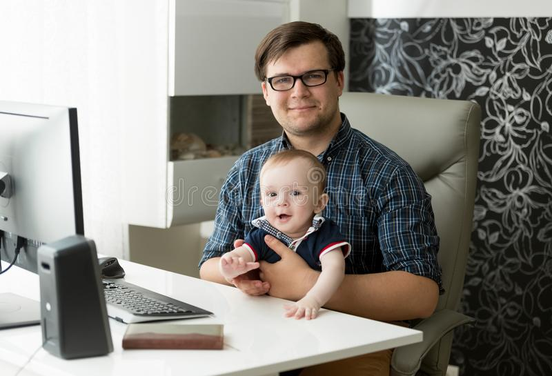 Porträt des lächelnden jungen männlichen Freiberuflers, der im Innenministerium sitzt und seinen einjährigen Babysohn hält lizenzfreies stockbild