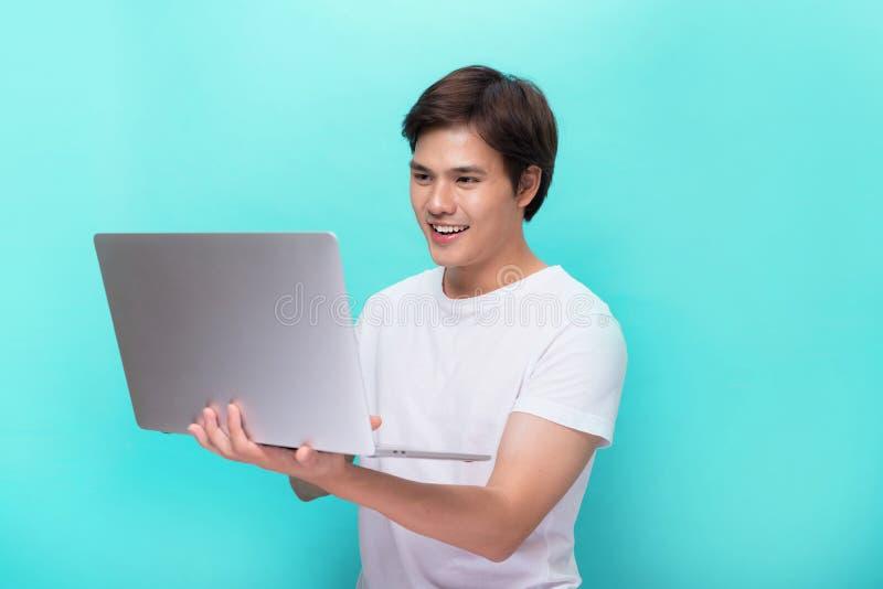 Porträt des lächelnden jungen Mannes mit dem Laptop lokalisiert auf Blau lizenzfreies stockbild