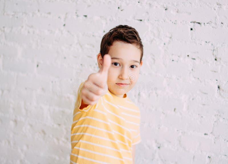 Porträt des lächelnden Jungen des netten Tweens in gelben T-Shirt Shows greifen oben lokalisiert auf weißem Backsteinmauerhinterg stockbilder