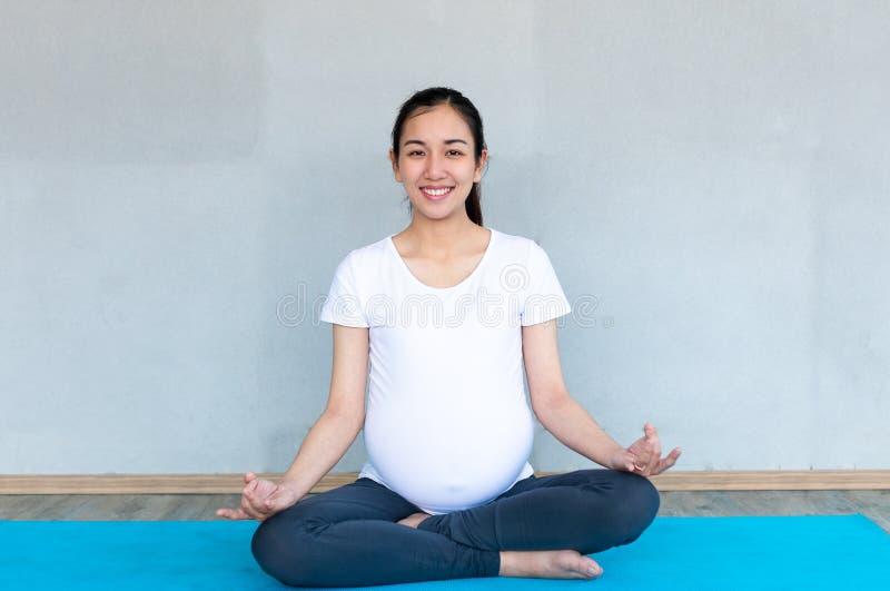 Porträt des lächelnden jungen schwangeren Eignungsmodells, das Yoga- oder pilatestraining, sitzend in der einfachen Haltung tut lizenzfreies stockfoto