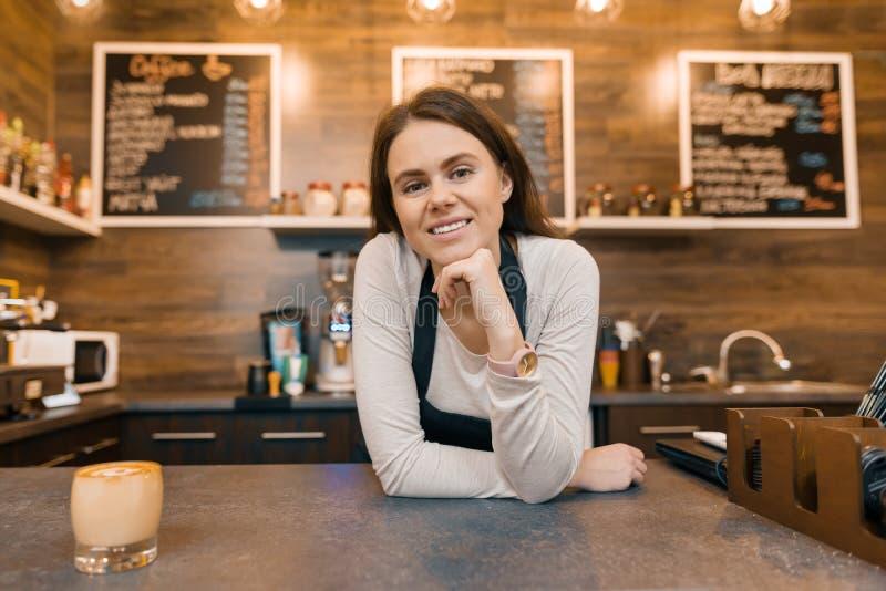 Porträt des lächelnden jungen weiblichen Kaffeestubeinhabers, überzeugte Frauenstellung am Zähler lizenzfreies stockfoto